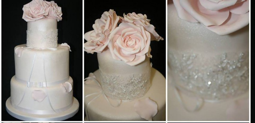 Weiße Hochzeitstorte mit rosa Rosen auf der Spitze