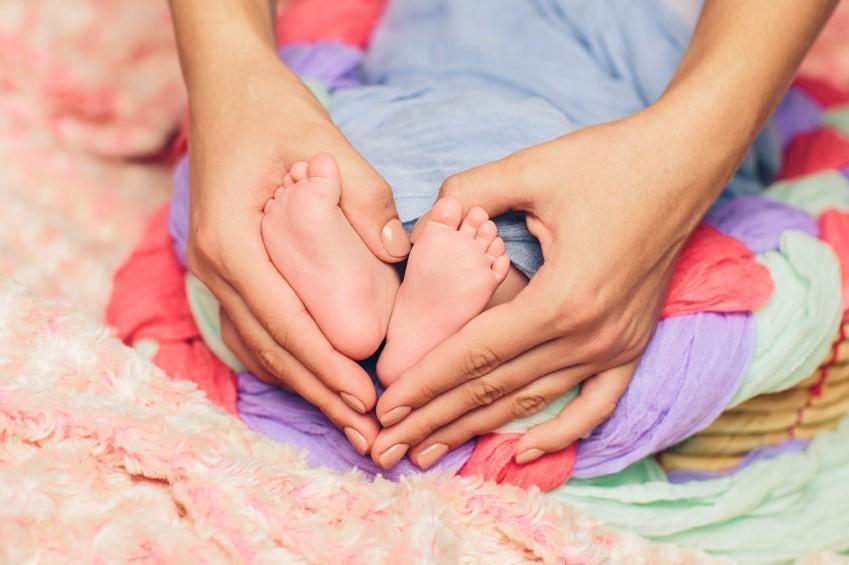 Babyfüße in den Händen der Mutter