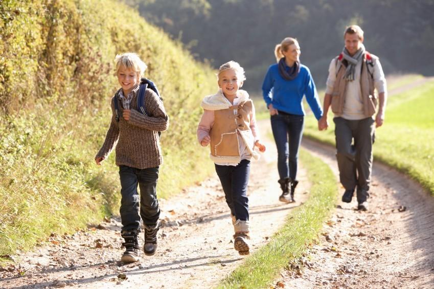 Familie mit zwei Kindern auf Feldweg im Herbst