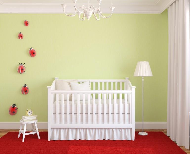 Kinderzimmer mit weißer Ausstattung, grüner Wand und rotem Teppich