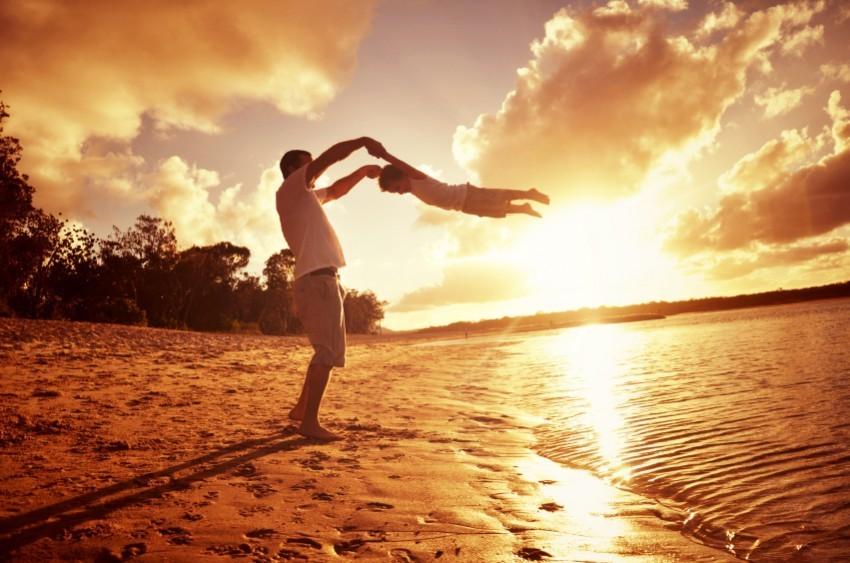 Vater schwingt Sohn am Strand im Sonnenuntergang