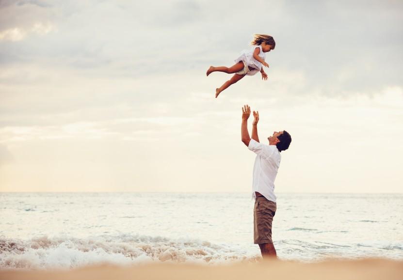 Vater am Strand wirft Tochter in die Luft
