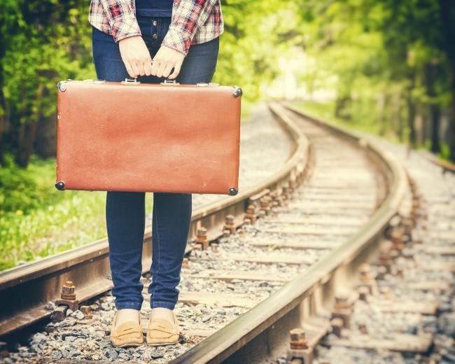 Mädchen steht mit altem Koffer auf Eisenbahnschienen