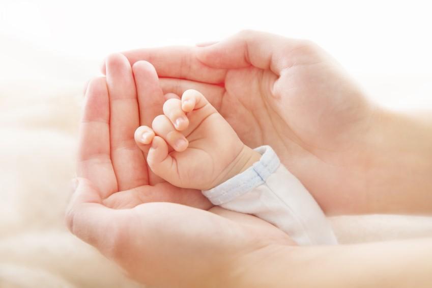 Neugeborenenhand in Händen der Mutter