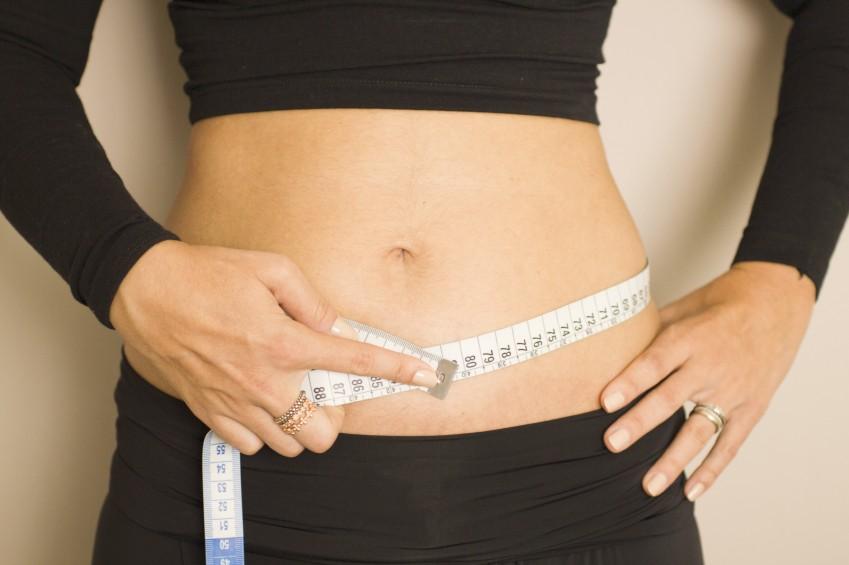 Maßband um Bauch einer Frau