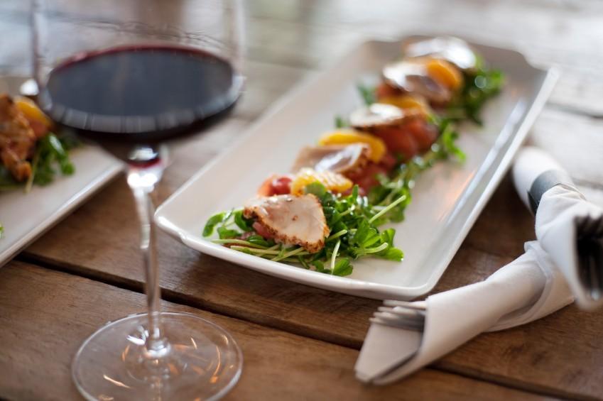 Weinglas und Platte mit edlem Fischsalat