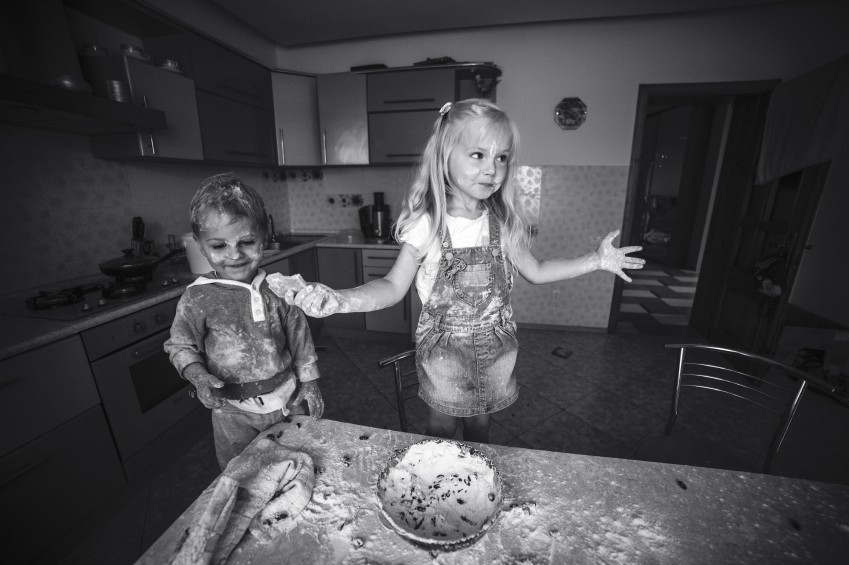 Kids is playing with flour in the kitchen
